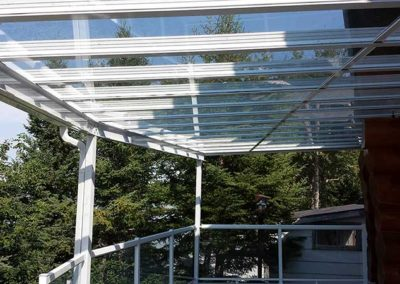 Side view of all glass patio cover on raised deck