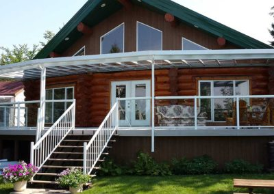 Large all glass patio cover and glass railings on log house