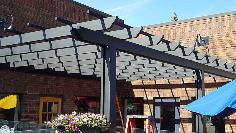 Aluminum pergola in dark colour on a restaurant patio