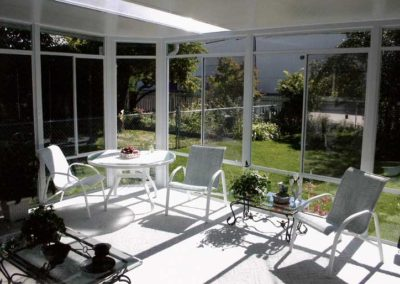 Interior view of glass walled sunroom with skylight