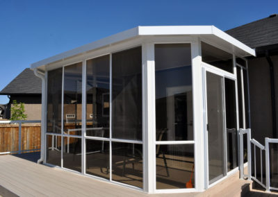 Aluminum sunroom with glass walls and screens