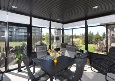 Interior view of a 3 season sunroom with dark panels and aluminum