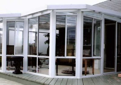 Custom shape sunroom with glass walls and roof