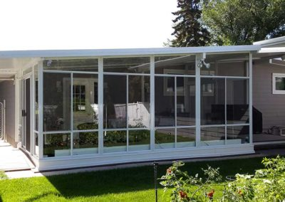 White aluminum sunroom all glass walls in summer