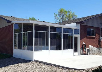 White aluminum sunroom with high ceilings, glass walls, concrete patio