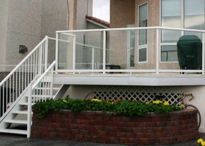 Glass railings around raised deck and stairs with white picket railings.