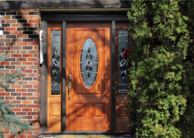 A vibrant medium stained wood door on a brown brick house.