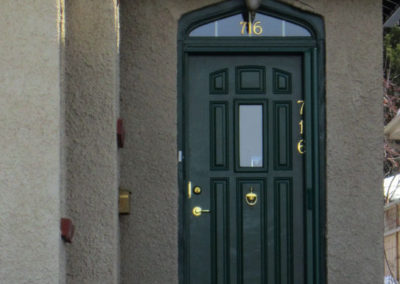 A green door on a stucco house with a little window above the door.