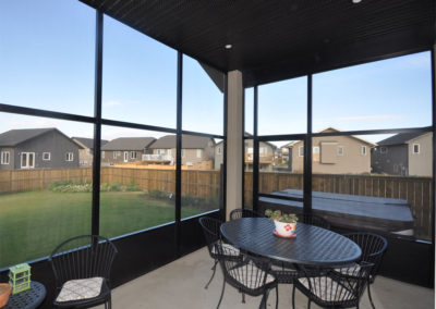Dark coloured aluminum screen room interior overlooking backyard