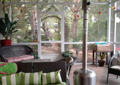View of forest-like backyard from aluminum screen room