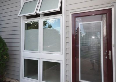 Burgundy coloured door and windows that open and have built-in blinds